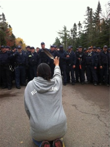 A M'ikmaq woman places her body in front of guns.